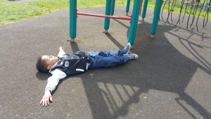 Child collapsed next to climbing frame