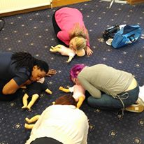 Group of adults practising CPR on dolls