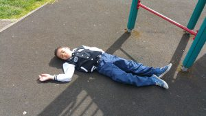 Child lying on the ground next to a climbing frame