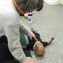Course attendee practising CPR on baby dummy