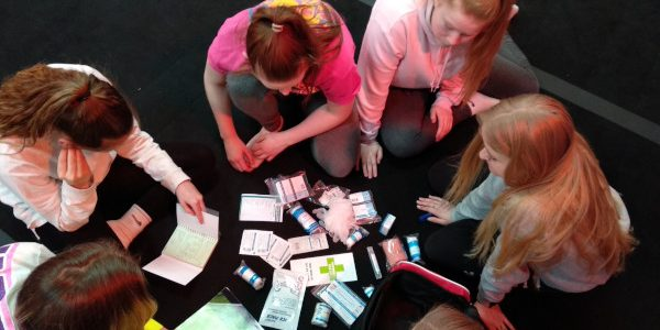 Group of women sat in a circle studying the contents of a first aid kit